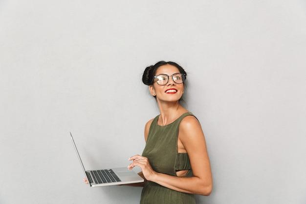 Retrato de uma jovem sorridente isolada, usando laptop, olhando para longe