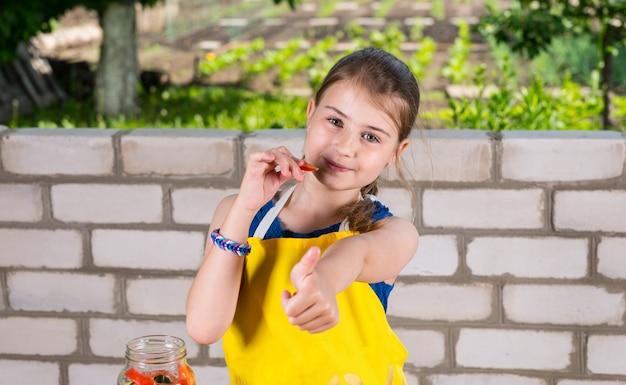 Retrato de uma jovem sorridente mordiscando pimenta e mostrando o polegar para a câmera