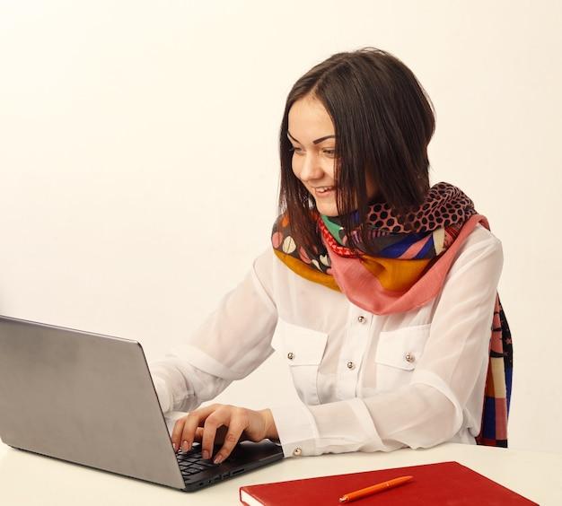 Retrato de uma jovem sorridente, mulher de negócios usando o laptop no escritório