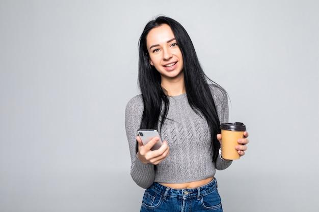 Retrato de uma jovem sorridente na mensagem de mensagem de camisa no telefone celular e segurando a xícara de café para ir isolado na parede cinza
