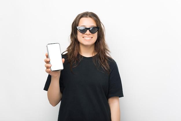 Retrato de uma jovem sorridente na moda em uma camiseta preta usando óculos escuros e mostrando uma tela em branco no telefone