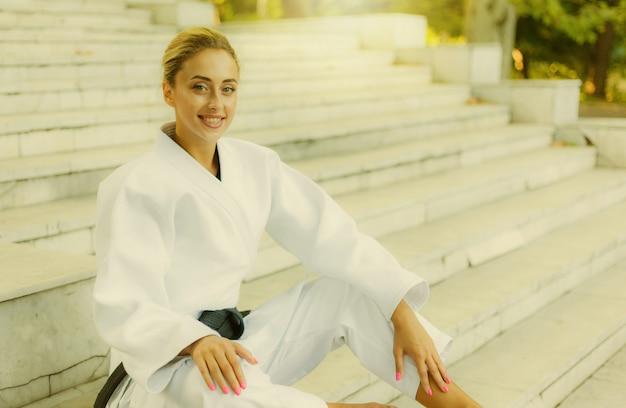 Retrato de uma jovem sorridente no quimono branco com faixa preta. mulher de esporte sentada na escada ao ar livre. artes marciais