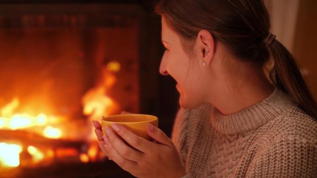 Retrato de uma jovem sorridente, olhando para o fogo no firepalce e bebendo chá quente à noite