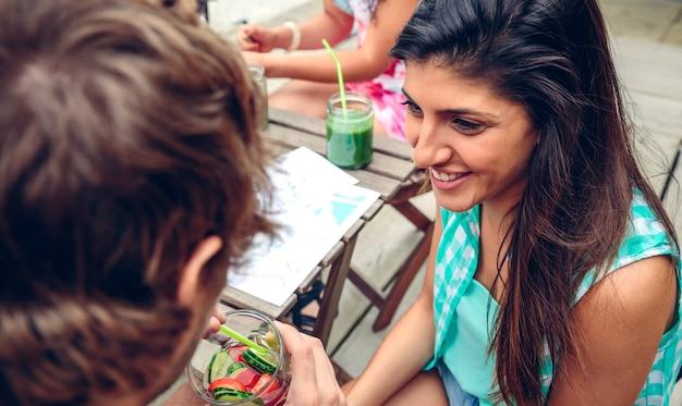 Retrato de uma jovem sorridente, olhando para um homem bebendo um coquetel de água com infusão ao ar livre em um dia de verão