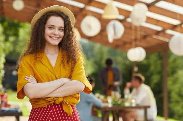 Retrato de uma jovem sorridente posando ao ar livre no verão com amigos e familiares, desfrutando de um jantar no terraço