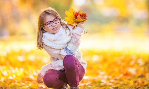 Retrato de uma jovem sorridente que segura na mão um buquê de folhas de bordo de outono