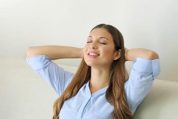 Retrato de uma jovem sorridente relaxando com os olhos fechados em um sofá, depois do trabalho em casa relaxando.