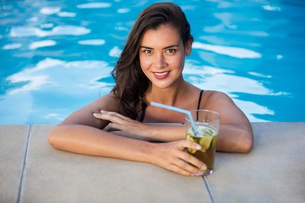 Retrato de uma jovem sorridente relaxando na piscina