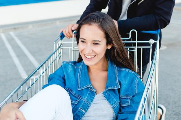 Retrato de uma jovem sorridente se divertindo dentro de um carrinho de compras