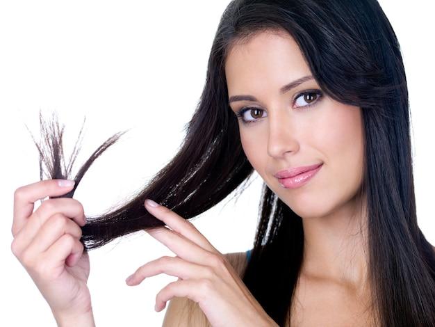 Retrato de uma jovem sorridente, segurando as pontas de seus longos cabelos castanhos - branco