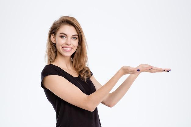 Retrato de uma jovem sorridente segurando copyspace nas palmas das mãos, isoladas em um fundo branco