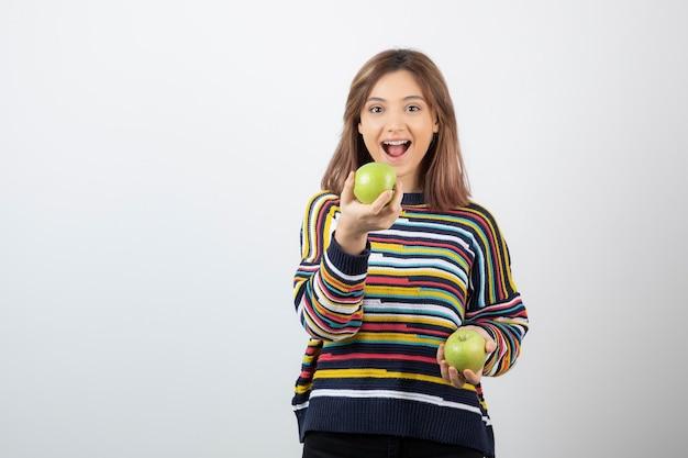 Retrato de uma jovem sorridente segurando duas maçãs verdes frescas.
