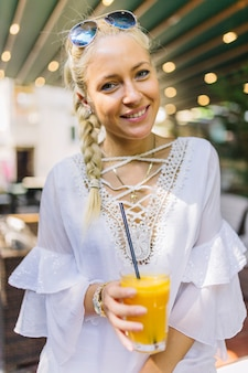 Retrato de uma jovem sorridente segurando o copo de suco com canudo nele