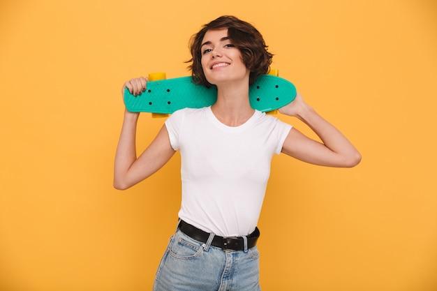 Retrato de uma jovem sorridente, segurando o skate