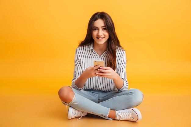 Retrato de uma jovem sorridente, segurando o telefone móvel