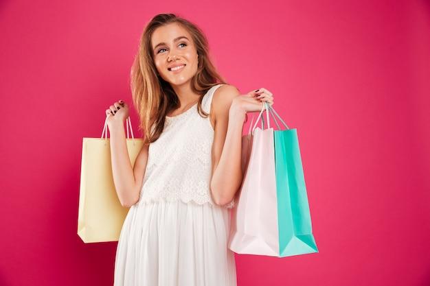 Retrato de uma jovem sorridente segurando sacolas de compras