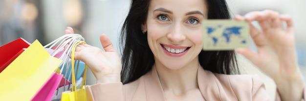 Retrato de uma jovem sorridente segurando um cartão do banco de crédito e sacolas de compras nas mãos