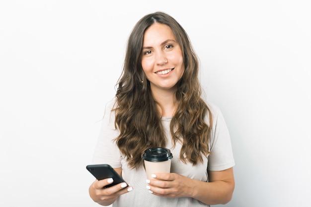 Retrato de uma jovem sorridente segurando um smartphone e uma xícara de café de papel