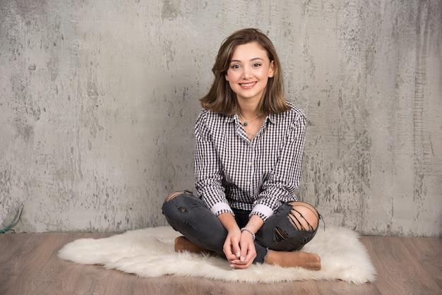 Retrato de uma jovem sorridente, sentada no chão e posando.