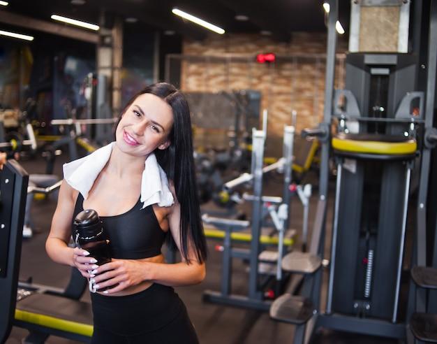 Retrato de uma jovem sorridente sportswomanin alegre no sportswear e toalha em volta do pescoço, garrafa de água na mão no ginásio