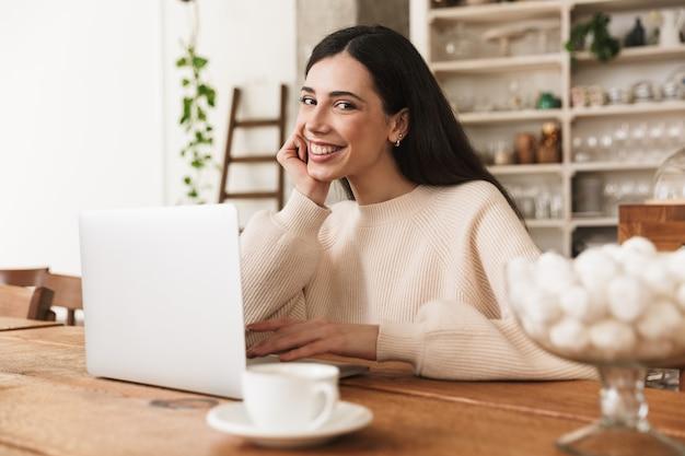 Retrato de uma jovem sorridente tomando café e usando o laptop na cozinha de casa