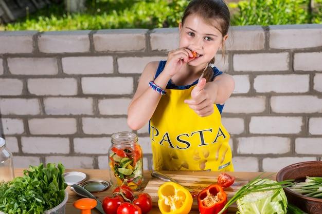 Retrato de uma jovem sorridente usando avental, mordiscando pimenta e dando os polegares para a câmera, garota cortando legumes em preparação para a conserva