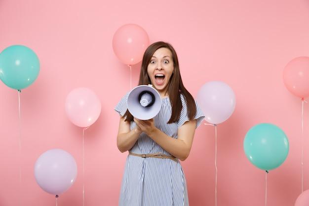 Retrato de uma jovem surpresa com a boca aberta, com um vestido azul, segurando o megafone, gritando no fundo rosa pastel com balões de ar coloridos. festa de aniversário, emoções sinceras de pessoas.