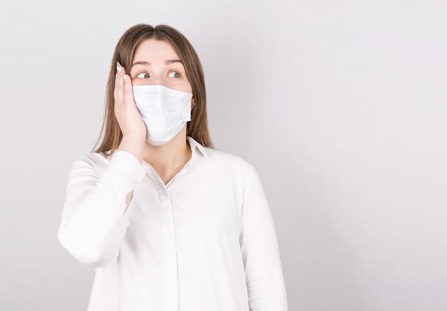 Retrato de uma jovem surpresa em uma máscara médica isolada sobre um fundo cinza. paciente jovem em pé contra o fundo da parede olhando para o lado, copie o espaço para o texto