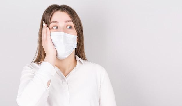 Retrato de uma jovem surpresa em uma máscara médica isolada sobre um fundo cinza.