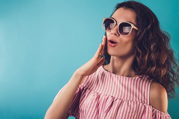 Retrato de uma jovem surpresa usando óculos escuros na parede azul