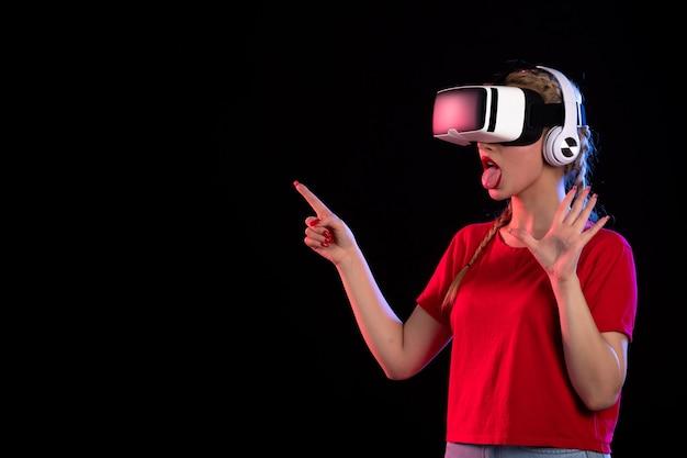 Retrato de uma jovem tocando vr em fones de ouvido em um ultrassom visual escuro