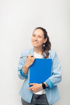 Retrato de uma jovem trabalhadora segurando uma papelada e sorrindo para a câmera