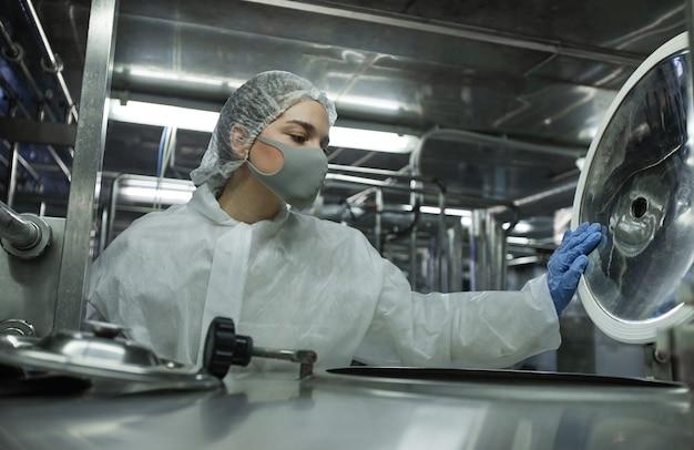 Retrato de uma jovem trabalhadora usando máscara e roupa protetora, abrindo barris enquanto trabalhava em uma fábrica de alimentos, copie o espaço