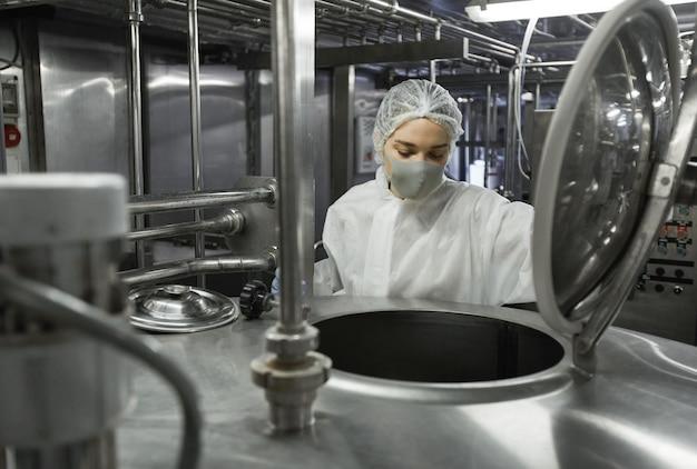 Retrato de uma jovem trabalhadora usando máscara enquanto opera a máquina de mistura na fábrica de produção de alimentos limpos, copie o espaço