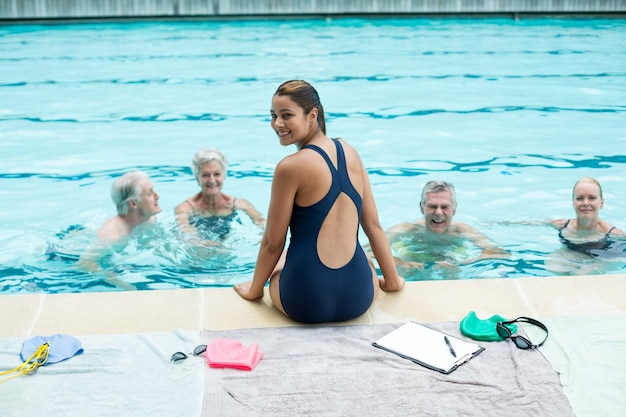 Retrato de uma jovem treinadora auxiliando nadadores sênior à beira da piscina