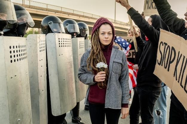 Retrato de uma jovem triste e temida em pé com margaridas entre uma multidão descontente com cartazes e a tropa de choque com escudos