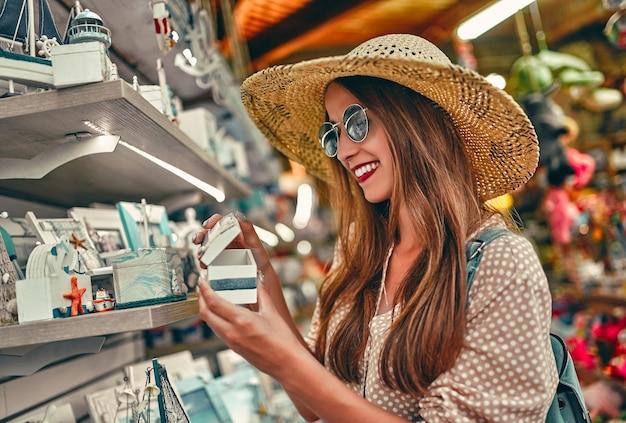 Retrato de uma jovem turista atraente com um chapéu de palha, blusa e óculos escuros, que caminha ao redor do mercado da cidade e seleciona as caixas decorativas. o conceito de turismo, viagens.