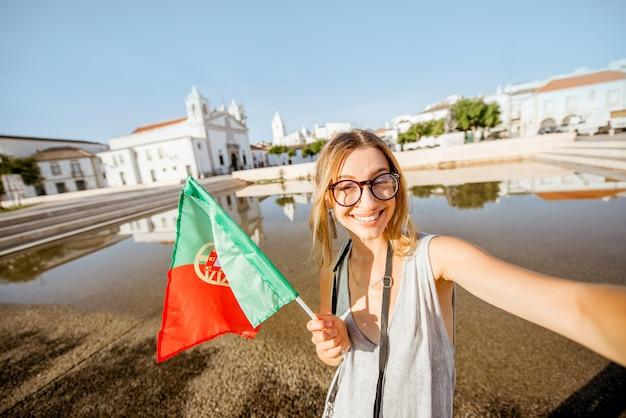 Retrato de uma jovem turista com bandeira portuguesa viajando na cidade de lagos, no sul de portugal