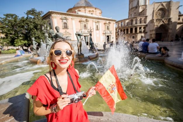 Retrato de uma jovem turista vestida de vermelho com bandeira espanhola perto da fonte na praça central da cidade de valência, espanha.