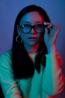 Retrato de uma jovem usando e tocando óculos com luz vermelha e azul