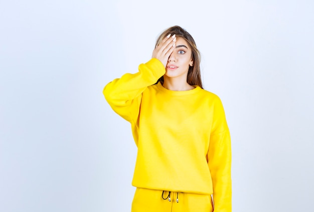 Retrato de uma jovem vestida de amarelo em pé e cobrindo o olho