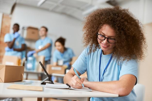 Retrato de uma jovem voluntária de uniforme azul fazendo anotações enquanto trabalhava no projeto de doação