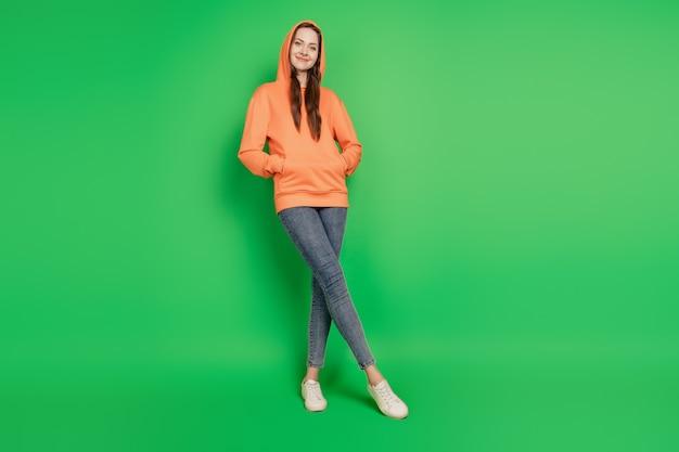 Retrato de uma linda adolescente elegante hippie senhora posando com capuz sobre fundo verde