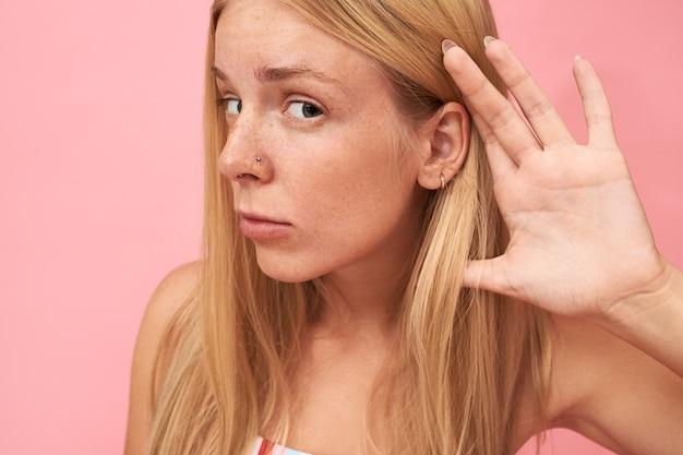 Retrato de uma linda adolescente loira com cabelo comprido solto, sardas e piercing no nariz colocando a mão em sua orelha, com olhar curioso