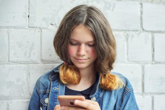 Retrato de uma linda adolescente sorridente de 14, 15 anos com smartphone