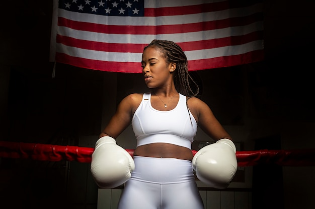 Retrato de uma linda atleta de boxe afro-americana no ringue de boxe com a bandeira dos estados unidos
