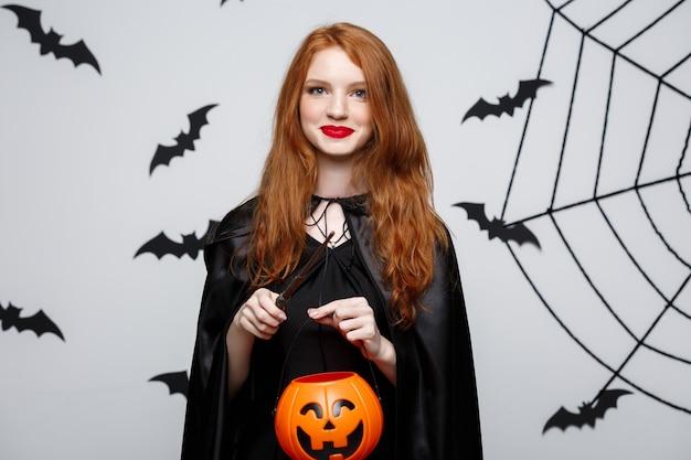 Retrato de uma linda bruxa caucasiana segurando abóbora laranja para celebrar o halloween.