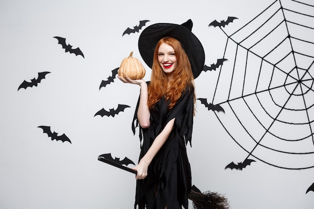 Retrato de uma linda bruxa caucasiana segurando uma abóbora para comemorar o dia das bruxas