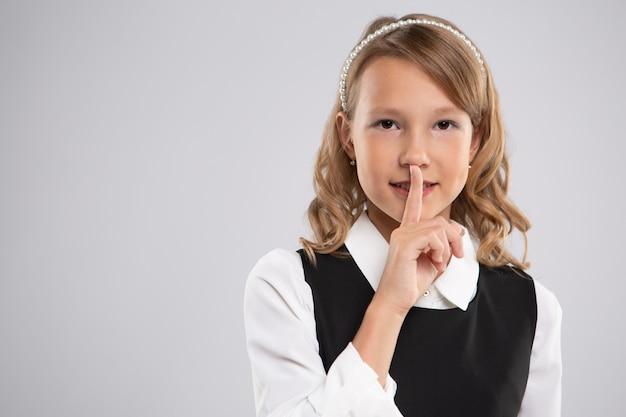 Retrato de uma linda colegial que colocou o dedo nos lábios para criar silêncio.