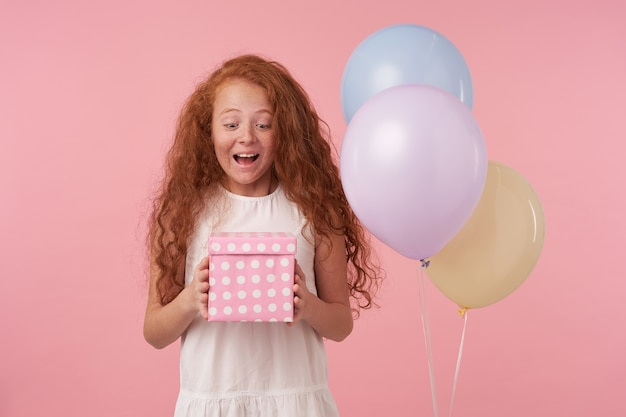 Retrato de uma linda criança alegre feminina em um vestido branco, ficando animada e surpresa ao receber um presente de aniversário, sorrindo alegremente e segurando o presente nas mãos, isolado sobre um fundo rosa